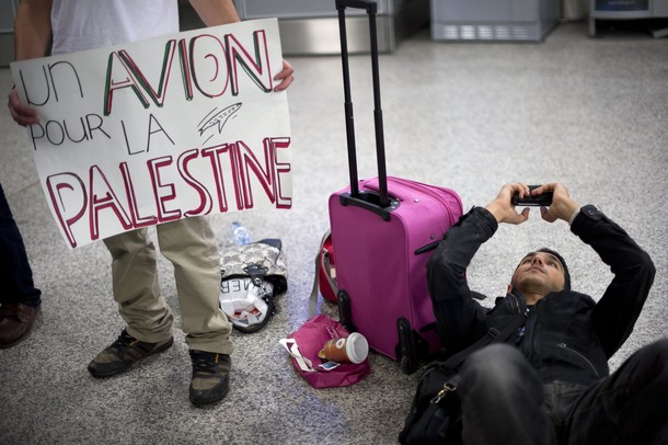 "A Pro-Palestinian activists holds a placard reading in French ""A plane for Palestine"" during a protest at Geneva airport on April 15, 2012 in Geneva. Several dozen pro-Palestinian activists protested at Geneva airport, saying authorities prevented them from boarding a Tel Aviv-bound flight as part of a ""fly-in"" that Israel has vowed to block.    AFP PHOTO/ FABRICE COFFRINI"