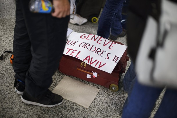 "Pro-Palestinian activists stand next to a placard reading ""Geneva, gets orders from Israel"" as they protest at Geneva airport on April 15, 2012 in Geneva. Several dozen pro-Palestinian activists protested at Geneva airport, saying authorities prevented them from boarding a Tel Aviv-bound flight as part of a ""fly-in"" that Israel has vowed to block.    AFP PHOTO/ FABRICE COFFRINI"