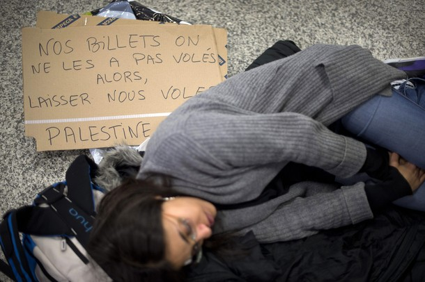 "A pro-Palestinian activist has a rest next to a placard reading ""We have not stolen our tickets so let us fly"" during a protest at Geneva airport on April 15, 2012 in Geneva. Several dozen pro-Palestinian activists protested at Geneva airport, saying authorities prevented them from boarding a Tel Aviv-bound flight as part of a ""fly-in"" that Israel has vowed to block.    AFP PHOTO/ FABRICE COFFRINI"