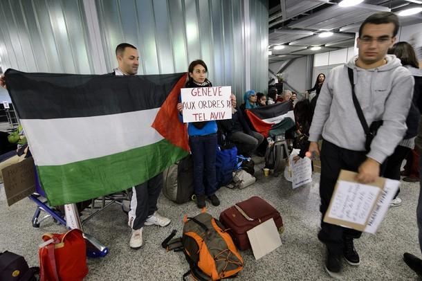 "Pro-Palestinian activists hold placards reading ""Geneva gets orders from Israel"" at Geneva airport on April 15, 2012 in Geneva. Several dozen pro-Palestinian activists protested at Geneva airport, saying authorities prevented them from boarding a Tel Aviv-bound flight as part of a ""fly-in"" that Israel has vowed to block.    AFP PHOTO/ FABRICE COFFRINI"