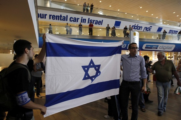 "Right-wing activists hold an Israeli flag in the arrival hall at Ben Gurion International Airport near Tel Aviv April 15, 2012. A pro-Palestinian ""fly-in"" to Tel Aviv got off to a slow start on Sunday after Israel scrambled to block activists from boarding flights in Europe. REUTERS/Ronen Zvulun"