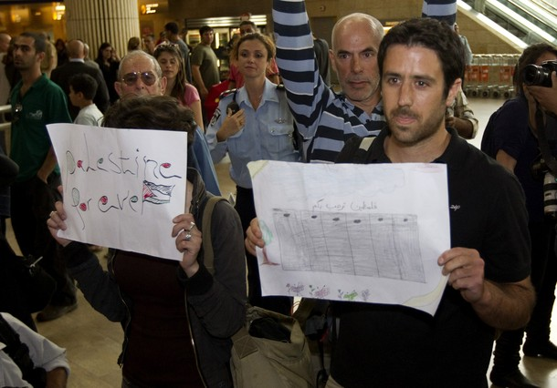"Israeli left-wing activist take part in a ""Welcome to Palestine"" fly-in at Ben Gurion airport near Tel Aviv on April 15, 2012 as hundreds of Israeli police, many undercover, were stationed at the airport to block the arrival of pro-Palestinian activists. Israel vowed to prevent entry  of activists, warning foreign airlines they would be forced to foot the bill for the activists' immediate return home in a move which saw many carriers toeing the line, prompting a furious response from passengers. AFP PHOTO/JACK GUEZ"